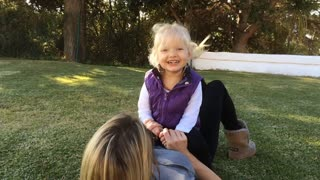 Daughter sitting on mother and laughing
