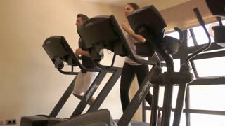 Dolly shot of couple running on treadmill at gym.