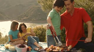 Dolly shot of family having barbecue picnic by lake in countryside.