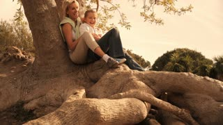 Dolly shot of grandmother and granddaughter sitting on tree root in park.