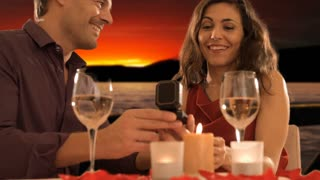 dolly shot of mid aged couple at dinner giving ring