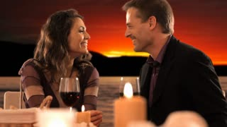 dolly shot of mid aged couple at dinner giving rose