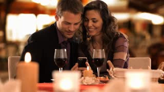 dolly shot of mid aged couple at dinner looking at phone