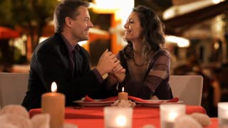dolly shot of mid aged couple at dinner