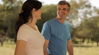 dolly shot of mid aged couple walking in countryside