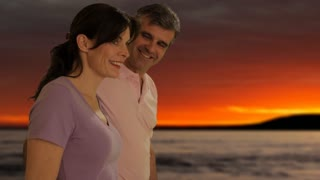 dolly shot of mid aged couple walking in sunset