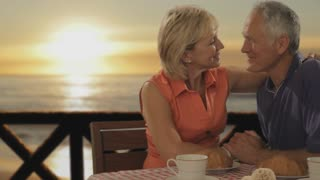 dolly shot of senior couple at beach cafe in sunset