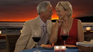dolly shot of senior couple at dinner in sunset giving rose