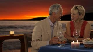 dolly shot of senior couple at dinner in sunset waiter serving wine