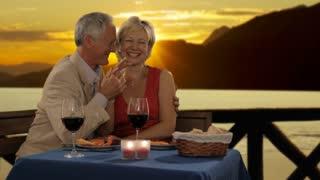 dolly shot of senior couple having dinner in sunset