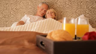 dolly shot of senior couple sitting in bed with breakfast in foreground