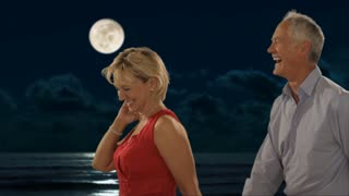 dolly shot of senior couple walking in moonlight