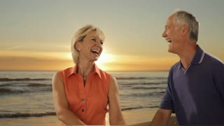 dolly shot of senior couple walking on beach with sunset and sea background