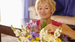 Dolly shot of woman arranging flowers.