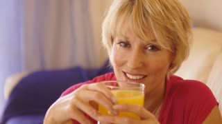 Dolly shot of woman drinking glass of orange juice.
