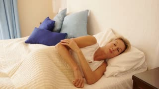 Dolly shot of woman in bedroom waking up and stretching.