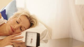 Dolly shot of woman in bedroom waking up to alarm clock.