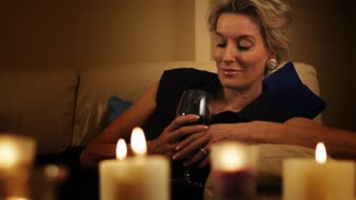 Dolly shot of woman lying on sofa with glass of wine in the evening