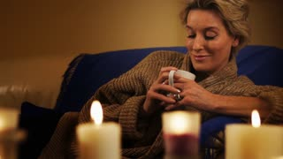 Dolly shot of woman lying on sofa with in the evening with beverage.