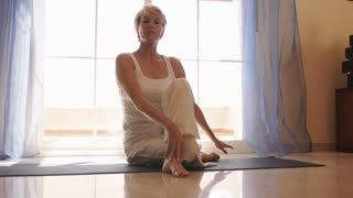 Dolly shot of woman practicing yoga in front of window at home.