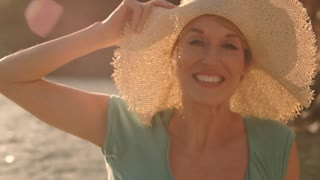 Dolly shot of woman sitting and relaxing on jetty at lakeside with hat smiling.