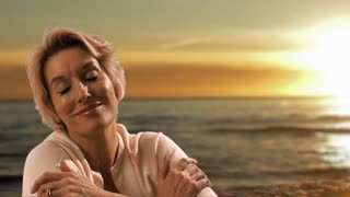 Dolly shot of woman sitting on beach at sunset.