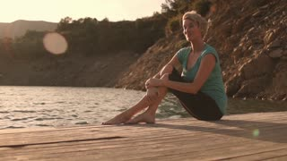 Dolly shot of woman sitting on jetty by lakeside relaxing.
