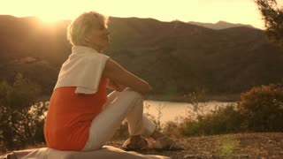 Dolly shot of woman sitting relaxing overlooking lake in sunset.