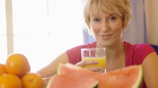 Dolly shot of woman with fruit in foreground drinking glass of orange juice.