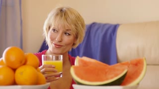 Dolly shot of woman with fruit in foreground holding glass of orange juice.