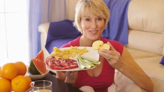 Dolly shot of woman with healthy fruit plate eating an apple.