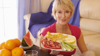 Dolly shot of woman with healthy fruit plate.