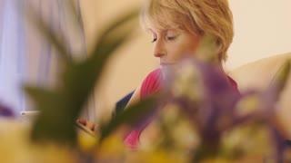 Dolly shot of woman working on tablet sitting on sofa at home.