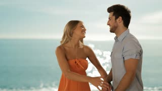 dolly shot of young couple hugging and twirling on beach
