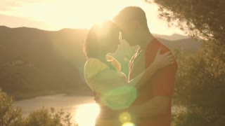 Dolly shot of young couple hugging overlooking lake in sunset.