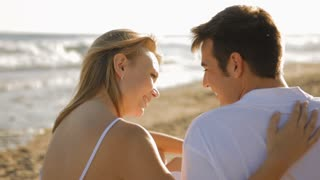 dolly shot of young couple sitting on beach