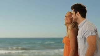 dolly shot of young couple walking on beach