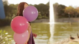 dolly shot of young girl with balloons in park