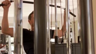 Dolly shot of young man exercising at gym.