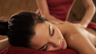 dolly shot of young woman having massage, candlelit background