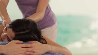 dolly shot of young woman having massage, sea background