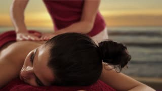 dolly shot of young woman having massage, sunset and beach background