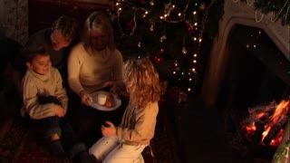 Family at Christmas putting out presents for Santa.