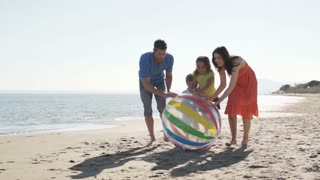 Family chasing beach ball along beach