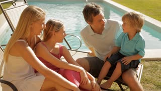 family group sitting by pool