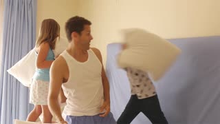 Family having a pillow fight in bedroom.