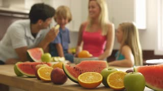 Family in kitchen eating healthy fruit.