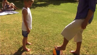 Family in park, father and son playing football