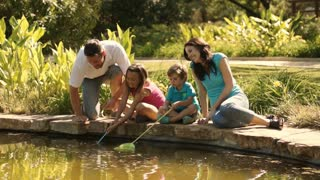 Family in park fishing with nets in lake.