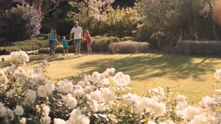 Family in park running towards camera.